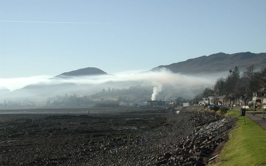 Rising smoke in Lochcarron (Scotland) forms a ceiling over the valley due to a temperature inversion.